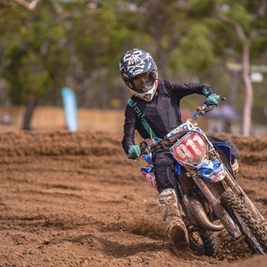Josh hall aboard his Yamaha 85cc dirt bike wearing the blackout pinned - Teal/Black jersey and panto combo